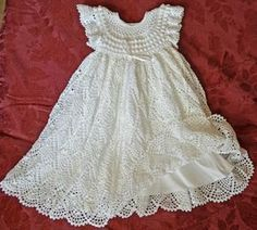 This unique Christening/Blessing dress is crocheted with #10 white cotton thread & accented with white ribbon around the waist. The detail of the bodice is adorned with rows of Popcorn stitching with a rounded neclkline of delicate crocheted lace. The bodice is finished with short, frilly sleeves. The skirt is very full with 2,000 yards of thread stitched in the beautiful pineapple stitch. The dress is very adjustable with a ribbon intertwined through the empire style waist so that i...