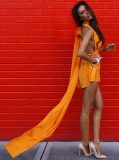 The gorgeous model Shiralee Coleman looks stunning in her bright neon pop Orange mini playsuit - styled halter neck with a large soft silk bow draping down her back for effortless style - by Sisters The Label