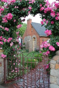 Iron gate set in stone wall and surrounded with a pink rose arbor...beautiful brick walk and lovely old brick home
