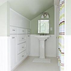 Beth Haley Design - bathrooms - sloped ceiling, bathroom sloped ceiling, green bathroom, green bathroom paint, green bathroom walls, pedestal sink, white pedestal sink, beveled mirror, bathroom mirrors, beveled bathroom mirror, built-ins, bathroom built-ins, built-in cabinets, bathroom built-in cabinets, shower curtain, striped shower curtain, white penny tiles, penny tile bathroom floors, white bathroom penny tiles, bathroom penny tiles, white bathroom penny tiles, double sconces, bathroom…