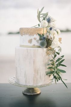 Modern two tiered wedding cake with gold metallic details olive branch foliage, thistle, rose detail cascading