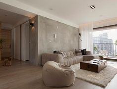 peinture à effet béton brut, tapis blanc super moelleux et canapé beige