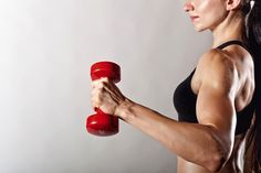 woman holding dumbbell flexing strong biceps