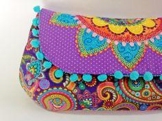 Clutch grande com a aba toda aplicada com retalhos e bordada, com acabamento em pompons. Valoriza qualquer produção!!! Possui um bolso…