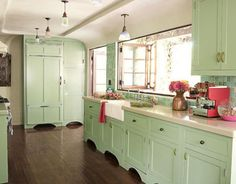 kitchen with green painted cabinets and light countertops and hardwoods