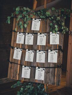 plan de table pour mariage en planches de bois vintage marron et petites listes invités blanches, écriture calligraphie en lettres noires, guirlande vert