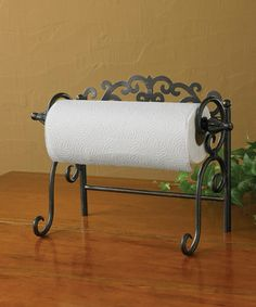Crafted from iron, this elegant paper towel holder lends a vintage vibe to kitchen décor, has arms that fold in for simple storage and can be wall mounted.