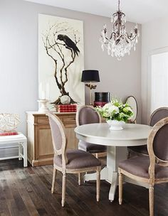 dining rooms - white pedestal dining table lilac purple French Louis chairs crystal chandelier crow art lilac purple walls paint color modern French dining room wood floors buffet lamp black shade white bench