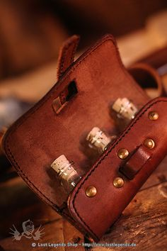 `.Small Leather Potion Bag with belt clip and three matching glass vials with cork stoppers.Size: approximately 7 x 14 cm