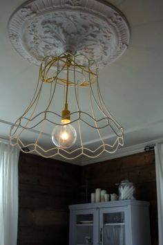 This is cool and cheep to do.  Find an old lamp shade at the thrift shop, strip the fabric down to its cage.  Spray paint it if you want.  Hard wire a pendant light fixture in ($20 at lowes) and tada!!  You can also buy knock off ornate ceiling pendants at Lowes for $20 to $60.