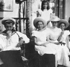Grand duchess Olga sits with her second cousins GD's Dmitry Pavlovich and Maria Pavlovna the younger, Tatiana, and Maria Nikolaevna standing.