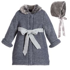 Girls coat and bonnet set by Foque. A navy blue and grey, mid-weight coat made in a soft knitted wool blend. It has a synthetic fur collar and popper fastenings, with an attached tie belt. It is fully lined in soft jersey for comfort. The bonnet has a soft synthetic fur feel to match the collar, a silky lining and ribbons to tie under the chin.