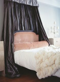 Bedroom with soft pink color palette, large round bolster, faux (or real) fur throw, cornice and curtain as headboard.