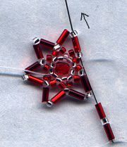 Star Ornament  Pick up 3 silver and go back through your point bead in the same direction, making a little circle. This is your picot.  Weave down into star, and back up to the next point, so that your thread is coming out of the silver point bead, and repeat with your 3 silver beads.