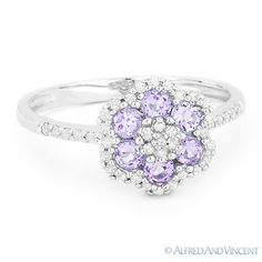 The featured ring is cast in 14k white gold and showcases a flower design petaled with purple amethyst gemstones and accentuated with round cut diamonds around the flower design and along the band.