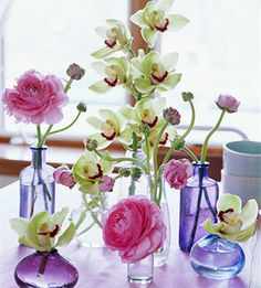 Fresh orchids or seasonal flowers in colored glass jars