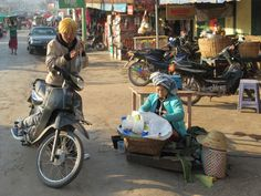 A motorcyclist in Kalaw, Myanmar (Burma), pauses to purchase food from a roadside vendor. Food, Meal, Eten, Hoods, Meals