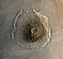 Olympus Mons (Latin for Mount Olympus) is a very large shield volcano on the planet Mars. By one measure, it has a height of nearly 25 km (16 mi). Olympus Mons stands almost three times as tall as Mount Everest's height above sea level.