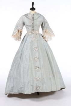 A pale blue silk gown with day and evening bodices, circa 1868, the evening bodice with puff sleeves, trimmed with bobbin lace and black velvet ribbon; the day bodice with pearlised buttons, long oval skirt trimmed with satin edged florets, matching belt, bust approx 86cm, 34in, waist 66cm, 26in