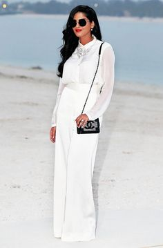 Princess Ameerah al-Taweel of Saudi Arabia steps out in a chiffon white top tucked into white wide-leg trousers, circle sunglasses, a statement necklace, and a black structured bag.
