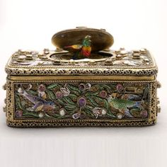 "German ""Jewel"" Mounted Enameled Silver Gilt Singing Bird Box. The silver filigree rectangular box cast with enameled birds in flowering vine with tulip, allover decorated with pearls and ""jewels"", the circular lid opening to reveal songbird with rotating perch (non operational). Late 19th/Early 20th Century."