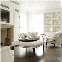 This is similar to what Jeff did on our fireplace, putting the tv inside a place above the fireplace.  whites + creams ... tufted ottoman ... tv in niche above fireplace