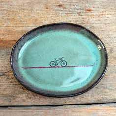 Small handmade oval plate with rustic green glaze, inlaid red line and hand drawn mountain bikeprint. Perfect for biscuits or a slice of cake.  Measures Length--> 17cm Width--> 13.5cm Height--> 2cm