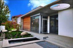 Ściana frontowa domu umiejętnie łączy niższą pracownię z wyższą częścią mieszkalną. Zasadniczą rolę gra tutaj zadaszenie z cienkiej płyty betonowej, spajającej obie bryły budynku.
