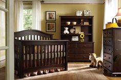 Dark wood arched back crib and matching dressers stand in this yellow nursery over hardwood flooring and brown rug.