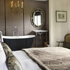 Hotel-style neutral bedroom with rolltop bath