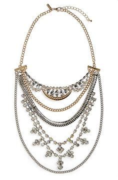 Bedazzle any ensemble with this two-tone layered statement necklace displaying a mix of chains with clear and iridescent crystals.