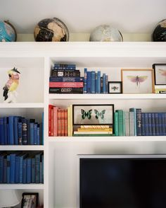 Built In Bookcase Photo - A collection of globes mixed with color-coded books