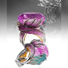 """Our """"Pisces Ring"""" features two  tropical lion fish hiding below a pink coral structure pictured by an impressive Kunzite .This flamboyant Ichthyic specie chaises its preys mimetizing between the underwater rocks .The large color-stone  is insured by the gem encrusted extensions of their fins whilst the two shaded creatures are embracing the finger with their nuances of pink sapphires , paraiba and diamonds . Discover the moving eye pupils, the hidden galleries and the carved tails !"""