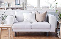 Uma sala em tons claros, com um sofa branco de 2 lugares e pernas em cinzento.