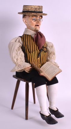 19th century automaton of an elderly male  modelled in Victorian style clothing, seated upon a stool, with revolving head and moving arms, holding a book.