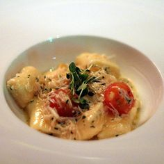 Barely solid ricotta gnudi are braced with tomatoes and a nest of stone crab meat at The Macintosh