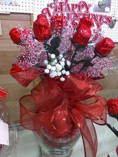 Valentine's Day Candy Arrangement. Chocolate Roses with plastic baby's breath. Cellophane gift wrapping used as backdrop and to hide Styrofoam at base of vase.