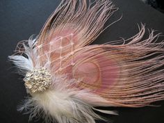 IF I used colored flowers in the bouquet then this would coordinate perfectly...  Wedding Bridal White Dusty Pink Peacock Feather Rhinestone Jewel Ivory Veiling Head Piece Hair Clip Fascinator Accessory. $35.00, via Etsy.