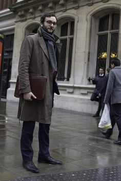 Tap into refined, elegant style with a dark brown trenchcoat and navy suit pants. Black leather oxford shoes will add a touch of polish to an otherwise low-key look.  Shop this look for $288:  http://lookastic.com/men/looks/scarf-trenchcoat-zip-pouch-dress-pants-oxford-shoes/7850  — Charcoal Scarf  — Dark Brown Trenchcoat  — Dark Brown Leather Zip Pouch  — Navy Dress Pants  — Black Leather Oxford Shoes