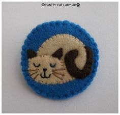 Felt Cat brooch/Pin This cat brooch has been hand made from felt and is 5 cm diameter. It has a silver safety brooch fitting stitched on to the back.