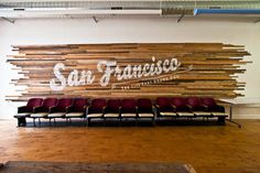 """We covered the main wall with 100 pieces of vintage hardwood flooring strips, then painted """"San Francisco: The city that knows how"""" on it using a projector as our stencil. We popped some 1930s movie seats (Craigslist score) in front of the lettering and voilà, we had a showpiece for the room."""