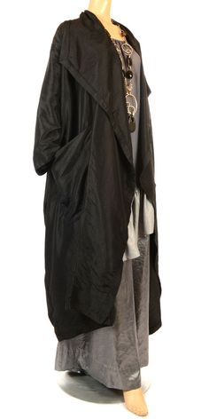 From this fabulous long established designer, this coat has a beautiful contemporary design. Oversize, wth a beautiful drape collar, ending in a single button fastening on the front, and then cutting away slightly down to the hemline. The dropped shoulder continues into a wide sleeve, and the coat is then finished with two oversize front pockets. The fabric, unlined and lightweight, in a subtle sheen black, with the lightest hint of a crush texture. Suitable for day or evening wear, and it…