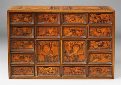 A mannerist display cabinet, Various fruitwoods and maple on oak and softwood, iron mountings. With 15 drawers surrounding a central door, decorated with birds and ruins in landscapes. In need of restoration, one side handle loose. H 62, W 91, D 37.5 cm., Attributed to Augsburg, late 16th / 1st quarter 17th C.