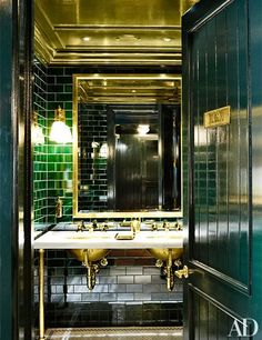 Emerald-green tile and brass details lend retro glamour to a washroom.