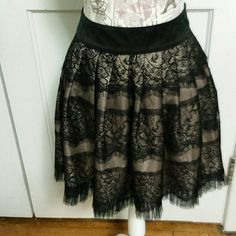 "Twenty One Skirt. Black lace over tan underskirt with black lace hem, zipper back, 2"" waistband, shell, 100 % poly, lining 59% nylon,  41% poly.  17"" long, waist lying is 15"". Twenty One Skirts"