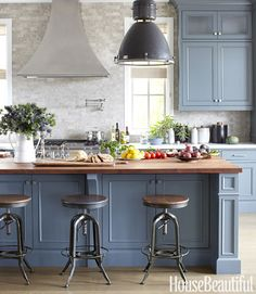 """""""The mahogany-topped island can easily fit 12 stools,"""" designer Parrish Chilcoat says. To set the cabinets and island apart, Chilcoat and Joe Lucas painted them two different shades: Farrow & Ball's Down Pipe, a warm gray, on the cabinets, and Benjamin Moore's cooler Chelsea Gray on the island in the kitchen of a California beach house. The backsplash is acid-washed Seagrass limestone from Classic Tile. VICTORIA PEARSON - HouseBeautiful.com"""