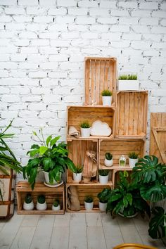 Amazing white room with beautiful green flowers. Wicker chair and a white fireplace. Silence, tranquility, peace in the house in the loft style. Wooden pallets in the interior Wooden Crates Wedding, Wooden Pallets, Crate Decor, White Fireplace, Plant Shelves, Modern Bedroom Design, Elegant Homes, Green Flowers, Home Decor Items
