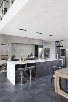 Raw and nordic expression in the kitchen - the white corian plate frames the kitchen island's black-fronted fronts, which makes the room appear brighter.