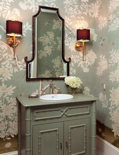 Chinoiserie powder room features gray green Asian wallpaper lined with a gold and black bamboo mirror illuminated by polished nickel sconces with black shades over a gray bamboo vanity fitted with a white porcelain sink and vintage style faucet.