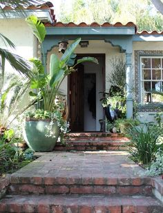 I like the teal/aqua trim contrast against the stucco walls and brick path. Fabulous charm